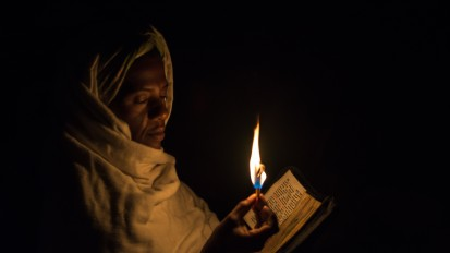 Pilgrim with candle and bible
